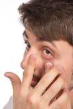 Opinión del primer del ojo marrón de un hombre mientras que inserta una c correctiva imagenes de archivo