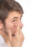 Opinión del primer del ojo marrón de un hombre mientras que inserta una c correctiva imagen de archivo libre de regalías