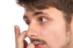 Opinión del primer del ojo marrón de un hombre mientras que inserta una c correctiva imágenes de archivo libres de regalías