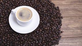 Opinión del primer desde arriba de una taza de café sobre los granos de café Imagen de archivo