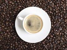 Opinión del primer desde arriba de una taza de café sobre los granos de café Fotografía de archivo libre de regalías