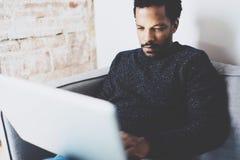Opinión del primer el hombre africano joven que usa el ordenador portátil mientras que sienta el sofá en su estudio coworking mod Foto de archivo libre de regalías