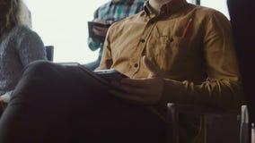 Opinión del primer el hombre de negocios joven que se sienta en el seminario y que hace notas en la tableta Hombre en la oficina  metrajes