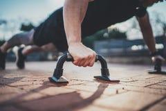 Opinión del primer el hombre hermoso del deporte que hace flexiones de brazos en el parque en la mañana soleada Concepto sano de  Fotos de archivo libres de regalías