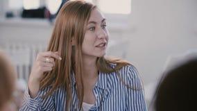 Opinión del primer el jefe femenino caucásico acertado hermoso joven que discute el trabajo con el equipo en el lugar de trabaj almacen de video