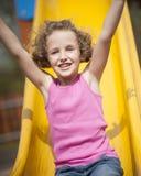 Opinión del primer la chica joven en diapositiva en patio Imagen de archivo libre de regalías