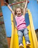 Opinión del primer la chica joven en diapositiva en patio Fotografía de archivo libre de regalías