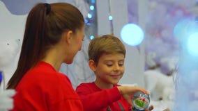 Opinión del primer la madre que da a su niño un presente, él lo está abriendo y feliz de recibir el globo de la nieve Navidad almacen de metraje de vídeo