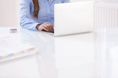 Opinión del primer la mujer hermosa que usa el ordenador portátil en el escritorio fotos de archivo