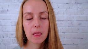 Opinión del primer la mujer joven que come un buñuelo y que bebe el café almacen de metraje de vídeo