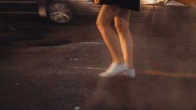 Opinión del primer la mujer joven que cruza el centro de la ciudad del camino del tráfico adentro de Nueva York por la tarde y qu metrajes
