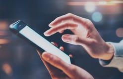 Opinión del primer la mujer que sostiene smartphone moderno en manos Muchacha que mecanografía en la pantalla móvil vacía Horizon Fotos de archivo libres de regalías