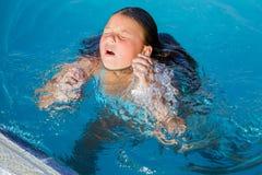 Opinión del primer la niña que sale de debajo el agua en la piscina Imagenes de archivo