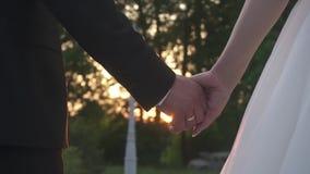 Opinión del primer los recienes casados que toman las manos y que las llevan a cabo en el fondo de la puesta del sol almacen de video