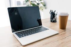 opinión del primer del ordenador portátil con la pantalla en blanco, la taza de café y efectos de escritorio fotografía de archivo libre de regalías