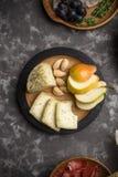 Opinión del primer del queso del caciotta con la almendra, peras en la placa de madera en fondo oscuro fotos de archivo