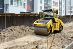 Opinión del primer sobre el rodillo de camino que trabaja en el nuevo sitio de la construcción de carreteras Fotografía de archivo