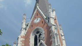 Opinión del primer sobre fachada de la iglesia del ladrillo rojo con la torre de reloj contra el cielo azul almacen de video