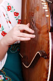 Opinión del primer sobre la mano de la muchacha que juega por bandura Imagen de archivo libre de regalías