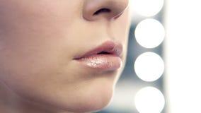 Opinión del primer un artista de maquillaje profesional que aplica el lápiz labial en los labios modelo del ` s que trabajan en s almacen de video