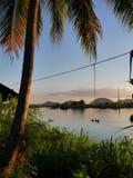 Opinión del río con el barco y palma y montañas Foto de archivo