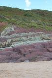 Opinión del retrato de la arena, rocas rojas en una playa Foto de archivo libre de regalías