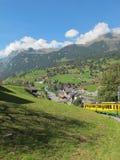 Opinión del tren y de la aldea de la rueda dentada en Suiza Imagen de archivo