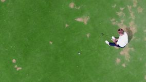 Opinión desde arriba de un jugador masculino que anota en el golf almacen de video