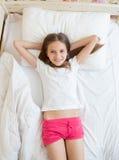 Opinión desde arriba sobre la muchacha linda que miente en cama y que mira la cámara Imagen de archivo libre de regalías