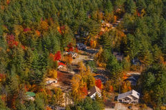 Opinión desde arriba sobre las pequeñas casas situadas en el bosque conífero del otoño Foto de archivo