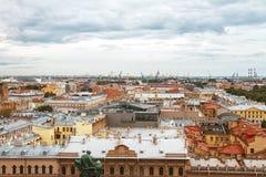 Opinión desde arriba sobre los tejados de las calles de St Petersburg y el puerto en un día nublado Imagen de archivo libre de regalías