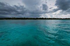 Opinión distante de la costa dominicana del agua en día nublado fotos de archivo