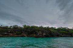 Opinión distante de la costa dominicana del agua en día nublado foto de archivo