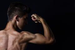 Opinión el adolescente muscular que dobla el bíceps en backgrou negro delantero Fotos de archivo libres de regalías