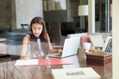 Opinión el adolescente que usa el ordenador portátil a través de ventana Imagen de archivo