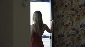 Opinión el blonde de ojos azules en el vestido rojo que presenta en el balcón en sitio metrajes