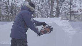 Opinión el escultor que talla el hielo movimiento Corte el hielo con una motosierra Corte y haga la escultura de hielo Tajar el h almacen de video