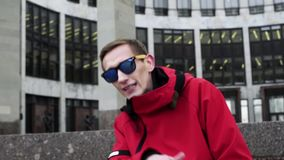 Opinión el hombre divertido en chaqueta roja y las gafas de sol que golpean al lado de columnas del granito metrajes