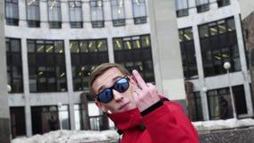 Opinión el individuo divertido en chaqueta roja y las gafas de sol que golpean al lado de columnas del granito metrajes
