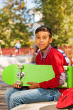 Opinión el muchacho árabe con la sentada verde del monopatín Imágenes de archivo libres de regalías