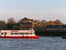Opinión el río Támesis, el barco, un pub, y la gente que tiene bebidas afuera en la puesta del sol imagen de archivo