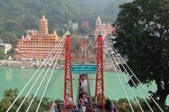 Opinión el terraplén del río de Ganga, el puente y Tera Manzil Temple, Trimbakeshwar de Lakshman Jhula en Rishikesh Imágenes de archivo libres de regalías
