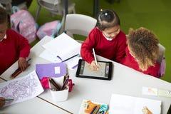 Opinión elevada dos colegialas infantiles que se sientan en una tabla, usando una tableta y una aguja en una sala de clase fotos de archivo
