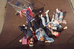 Opinión elevada los adolescentes que se divierten y que mienten con la bandera americana en parque del monopatín Imagenes de archivo