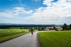 Opinión escénica la muchacha que camina abajo de un camino en un valle verde Foto de archivo libre de regalías