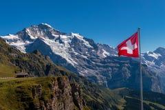 Opinión espectacular sobre Jungfrau famoso de Mannlichen y de la bandera suiza Fotos de archivo