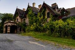 Opinión exterior de la puesta del sol/de la hora azul - mansión y hospital abandonados de Tioranda - Nueva York Foto de archivo