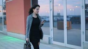 Opinión frontal la muchacha acertada del negocio con el cuello tatuado en chaqueta gris estricta y vestido negro que camina a tra almacen de video