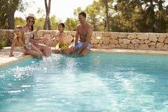 Opinión granangular la familia el las vacaciones que se divierten por la piscina imagenes de archivo