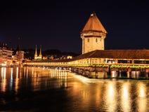 Opinión hermosa de la noche de la torre del puente y de agua de la capilla con la reflexión en el lago, Alfalfa, Suiza, Europa Foto de archivo libre de regalías